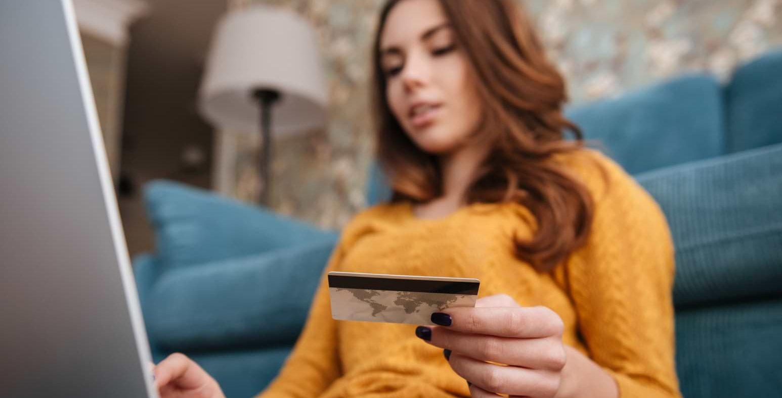 Kvinna med kreditkort framför dator
